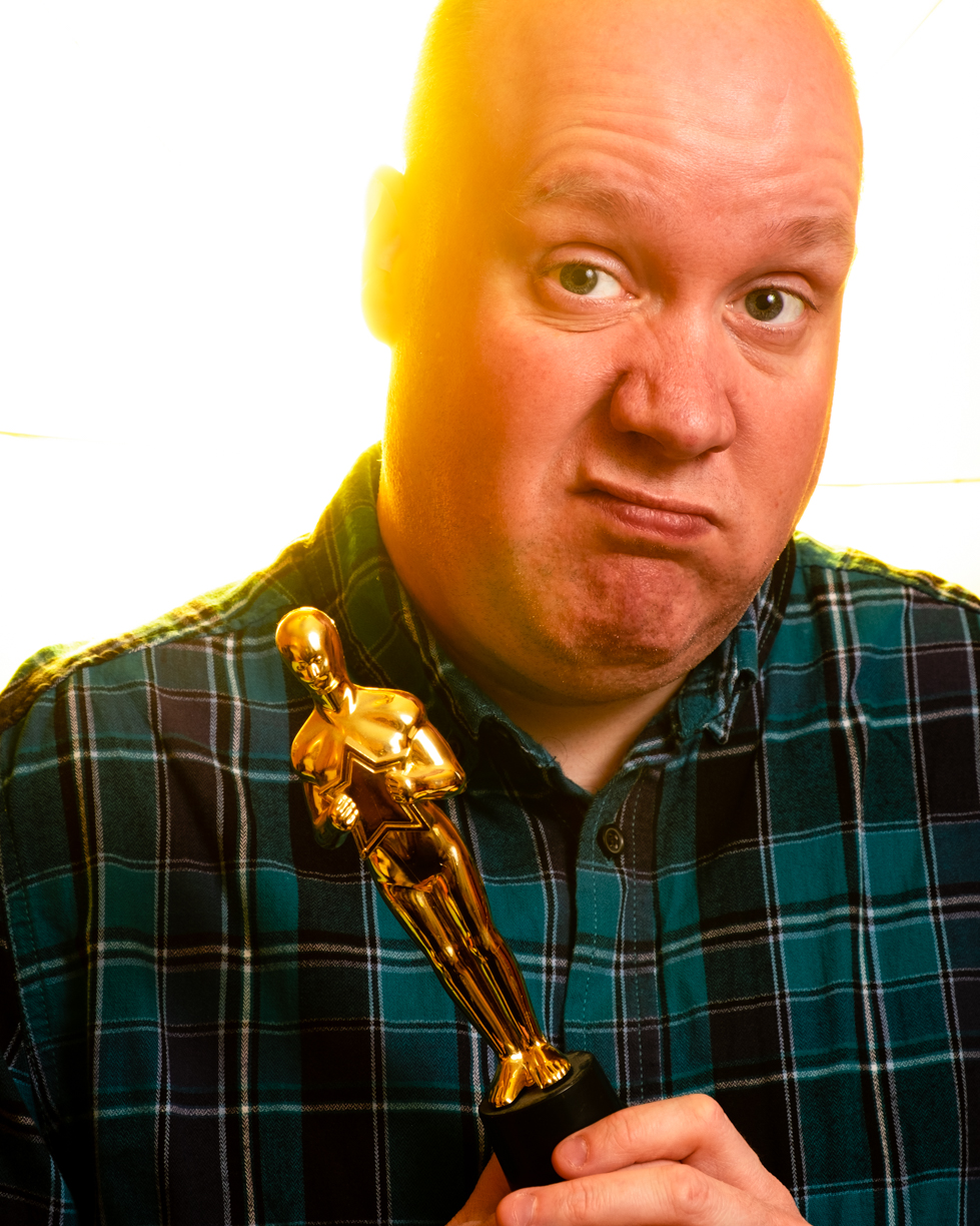 Me wearing a green chequered shirt, holding an oscar and pulling a face